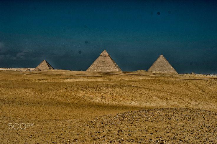 As grandes pirâmides. Elas sobem majestosa e inexplicavelmente do deserto ao lado de Gizé, no Egito. A Necrópole de Gizé é um sítio arqueológico localizado no planalto de Gizé, nos arredores do Cairo, Egito. Este complexo de monumentos antigos inclui os três complexos de pirâmides conhecidas como as Grandes Pirâmides, a escultura maciça conhecida como a Grande Esfinge, vários cemitérios, uma vila operária e um complexo industrial.   Fotografia: Shady Al-Mahmoudi em 500px.