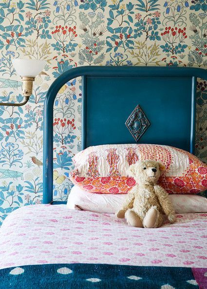 A floral wallcovering behind a navy blue twin bed.