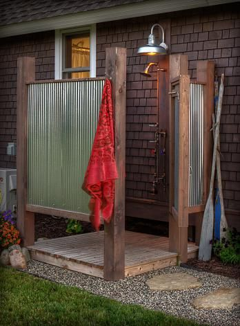 Corrugated metal sheets and pressure-treated wood make for a practical and inexpensive outdoor shower. Via Land's End Development