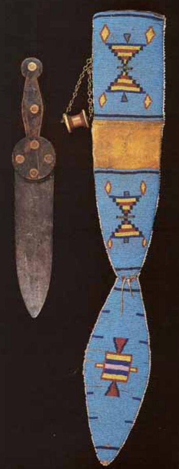 Нож и ножны, Черноногие. Период 1850-1875. Коллекция Fenn. Нож Baldwin Hill, без клейма на клинке. Материалы: дерево, железо, стеклянный бисер, медный бисер, медная цепь (на ней катушка ниток для крепления к ремню), сыромятная кожа. Длина кинжала 14.5 дюймов, длина ножен 25,5 дюймов. Joe Rivera.   Splendid Heritage.