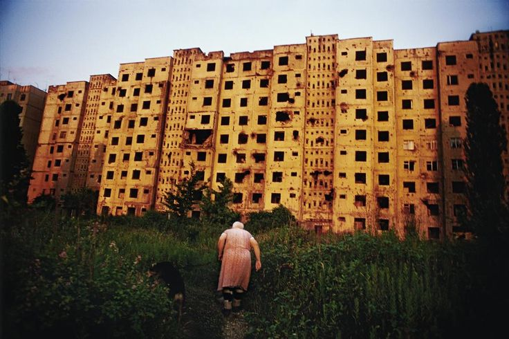 """Jonas Bendiksen GEORGIA. Abkhazia. Sukhum. 2005. Babushka """"Tanya,"""" an elderly ethnic Russian woman, heads back to her bombed out apartment building after walking her dog. Despite the damages, three apartments remain occupied in the building."""