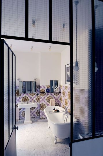 The bathroom window made of painted steel and laminated glass lets the light flow. A spirit of holiday highlighted by a claw feet bathtub, an antique mirror and tiles. The ceiling is dotted with spot lamps.