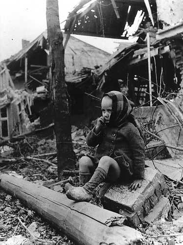 Late 1944. A child eating chocolate on a pile of rubble of what once was the house he lived in. Schijndel, The Netherlands.