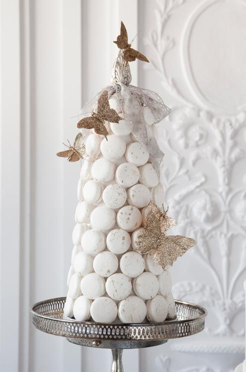 Hand-sculpted butterflies perch precariously on a tower of white macarons.