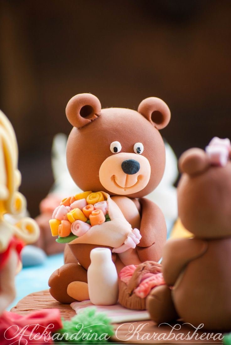Fondant teddy bear, on a romantic picnic, with a fondant flower bouquet. Part of a children's cake with fondant animals and fondant girl.