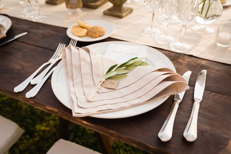 Olive branch and lace place setting. Wooden wedding day table with antique pink roses, pots of herbs, cream linen and vintage crystal glasses. Wedding day at Villa Nozzole. Tuscany, Italy