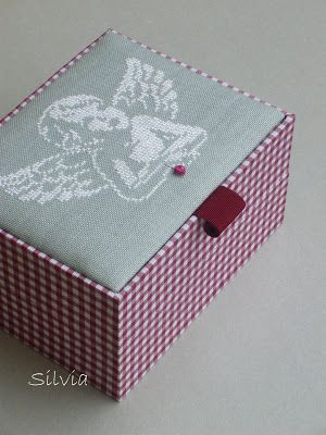 box covered in fabric and decorated with cross stitch