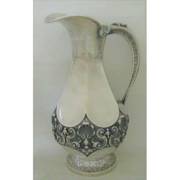 Bela jarra, estilo D. João, em prata contrastada, teor 800 milésimos, prateiro M.K, cinzelado em conchas, flores e volutas. Alt. 30 cm. Peso 1.065g. (Este item não se encontra no local da exposição).