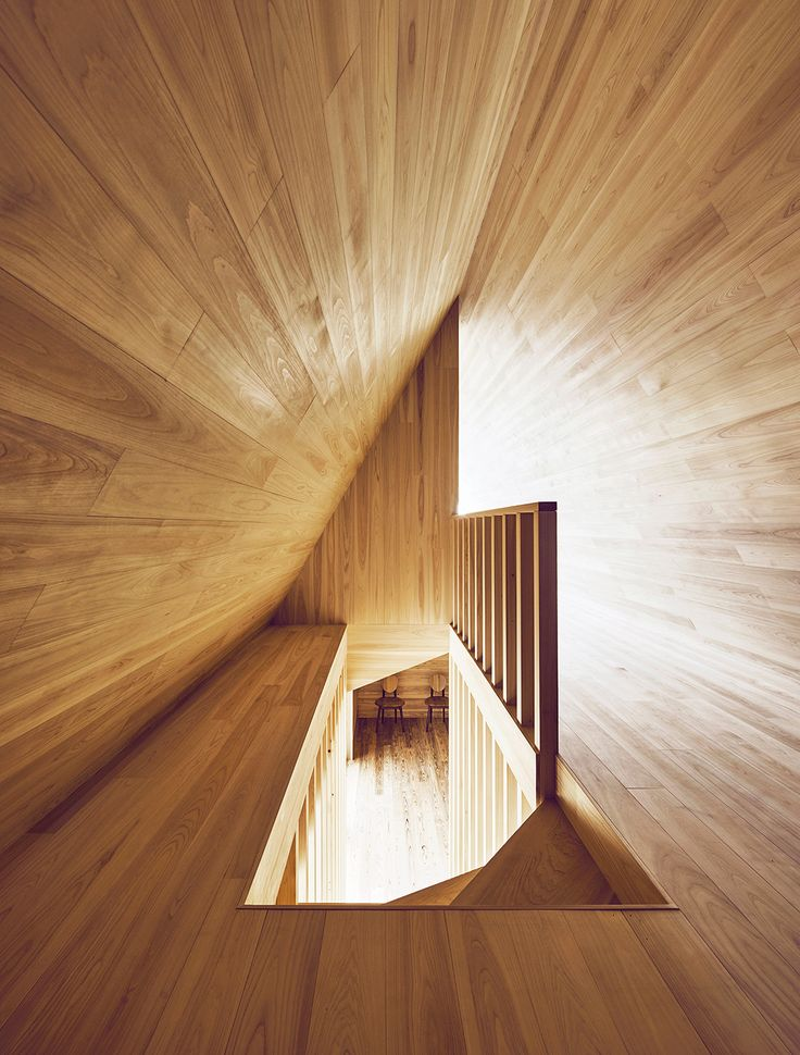 Looking down the stairway from above reveals the A shape of the upper floor and contrasting angles and tones of natural light.