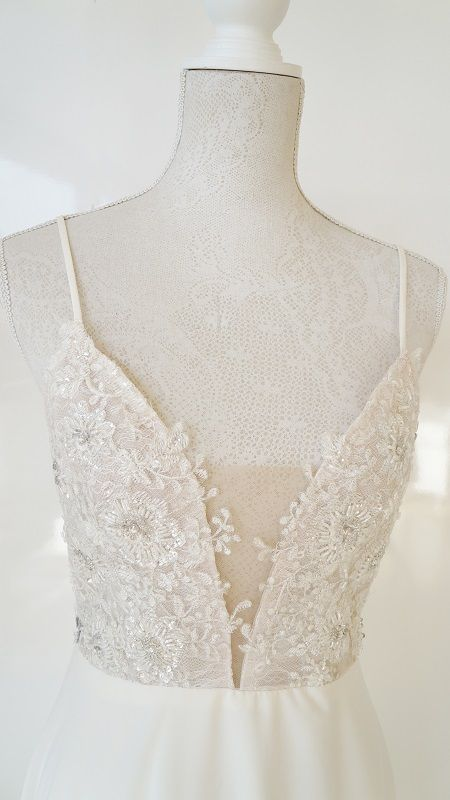 """Empire wedding gown with an elegant lace bodice, plunging neckline and open back.      Hire R7500    [call_two href=""""http://my.setmore.com/bookingpage/d355730c-585c-4a09-b166-240ebc71e9cc"""" colortext=""""#afafaf"""" background_color=""""#ffffff"""" font_size=""""32"""" label_button=""""Book appointment"""" label_size=""""30"""" class=""""call-to-action-two"""" animation_delay=""""0"""" animate="""""""" ][/call_two]"""
