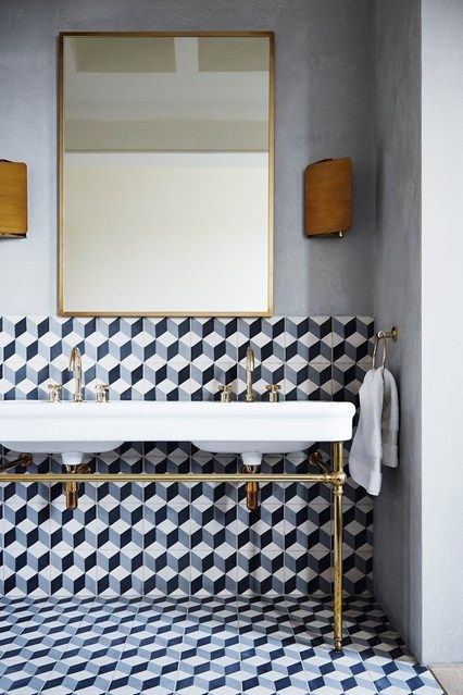 Stylish inspiration for bathroom vanity units and cabinets including this bathroom with reclaimed twin wash stand, brass taps and geometric tiles.