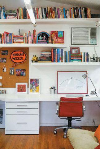 Dispostas em dois níveis, as prateleiras do home office da jornalista Antonia Leite Barbosa organizam livros fáceis de alcançar. Como a base da marcenaria é branca, o toque de cor fica por conta da cadeira vermelha da Tok&Stok, dos objetos e dos livros. A gravura é assinada por Oscar Niemeyer.
