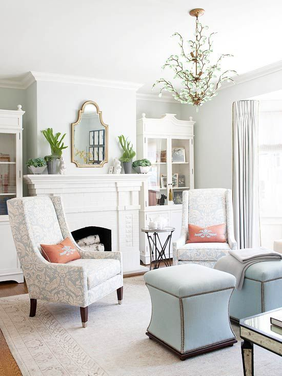 Love the fun shaped ottomans with nail head trim, the tall backed chairs with the orange pillows and the funky chandelier!