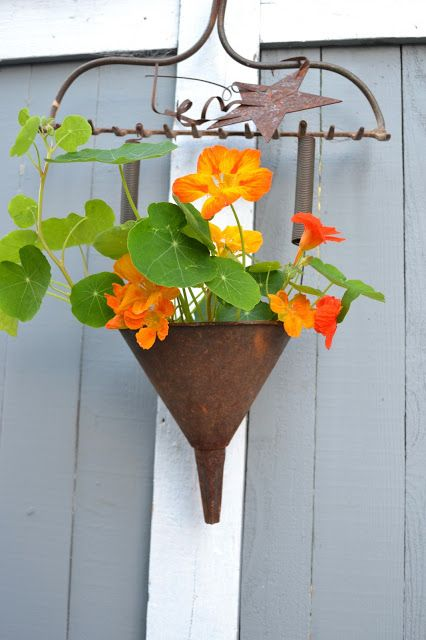 Rake holding a funnel planter filled with summer flowers. So fun!