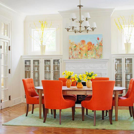 White with a punch of color    Fruit Flavors  Chairs covered in mango orange set the tone for this vibrant dining room. A pear green rug grounds the table and chairs in the middle of the spacious room, calls attention to the beautiful parquet floor, and offers a cool counterpoint to the warm and zesty orange. Both colors appear in the artwork over the fireplace.