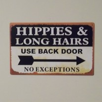 """Take a trip back in time with this retro metal sign that says """" Hippies and long hairs use back door, no exceptions """" Has two pre-drilled holes to hang on the wall and measures 16 inches by 10 inches."""