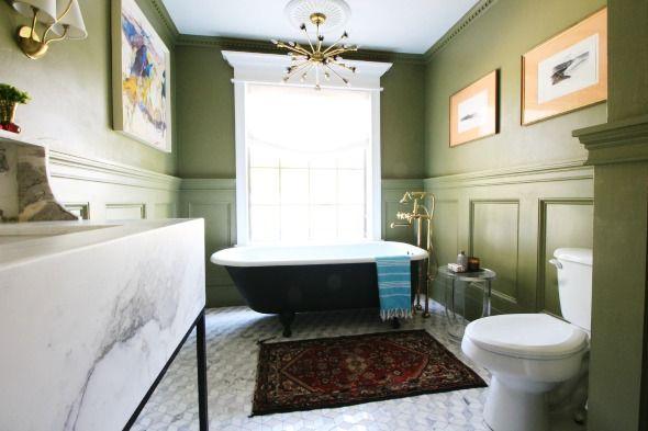 gorgeous bathroom with olive green walls and trim work, marble floors, black clawfoot tub, vintage sputnik style chandelier, custom marble and metal vanity
