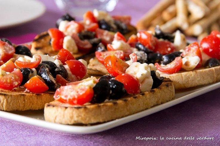 Semplici e veloci da preparare, le bruschette con Pachino, feta e olive nere all'origano saranno un gustoso e invitante antipasto per una cena all'aperto.