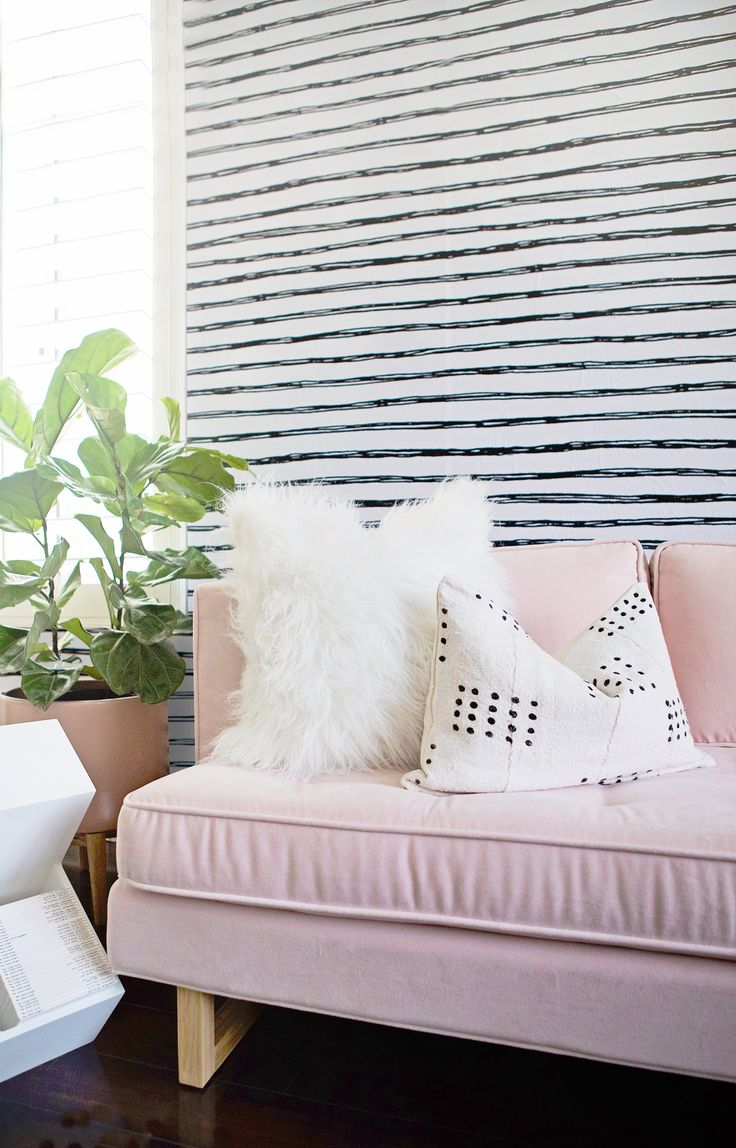 Black and White Striped Wallpaper and Pink Couch in Girl's Nursery