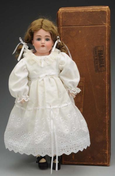 """Boxed Kestner """"Dainty Dorothy"""" Doll.    Bisque shoulder head mold 154 by J.D. Kestner, (speckling, nose rub), sleeping eyes, open mouth with teeth, replaced mohair wig; white kid body with rivet-jointed hips, knees and elbows with composition lower arms and legs; original """"Dainty Dorothy Kestner Kid Dolls"""" label. Original box (some wear and broken pieces) with """"Dainty Dorothy"""" label. Redressed with extra cotton print dress with Woolworth's tag.   Condition (Very Good). Size 18"""" T."""