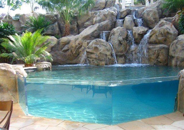 Piscina com borda em vidro e cascata com pedras artificiais