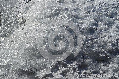 Ice and snow blocks melting under the winter sunrays.