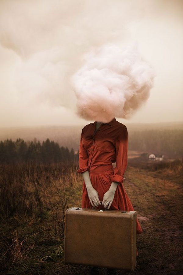 Girl in red dress with head in the clouds.