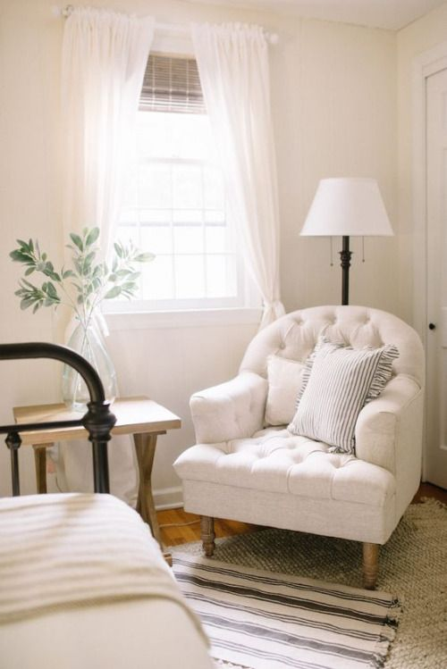 A cute little sitting nook in the bedroom. Love the tufted chair and demijohn with greenery.