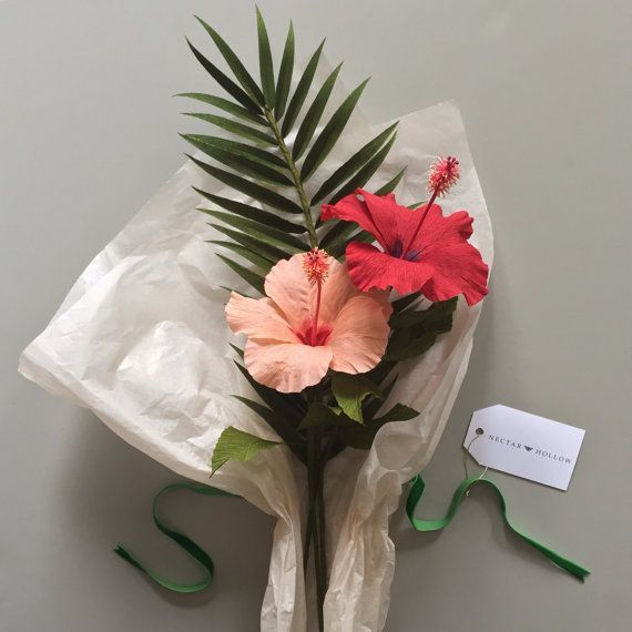 This tropical arrangement includes a coral hibiscus, cranberry hibiscus, and a palm frond. Perfect for adding an elegant, tropical vibe to your home or office decor, wedding, or anywhere you care to enjoy it. Made with extra-fine German crepe paper to accentuate the organic look, this bouquet will never wilt or die. Stems will be arranged and cut to accommodate a 7.5 vase and can be cut or bent to fit in any smaller vase you desire. (Vase not included). Dont see the colors youre looking for?…