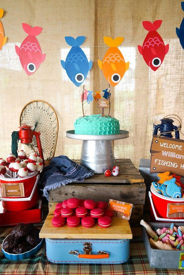 Festa Pescaria com mesa de doces rústica decorada com redes, peixinhos de papel, baldes e iscas.