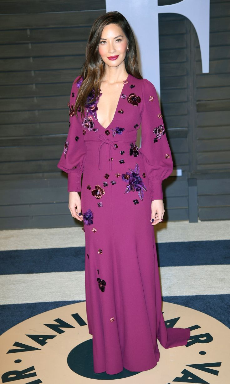 OLIVIA MUNN, Vanity Fair Party  in a deep berry gown with Dolman sleeves and sequin appliqués and matching lip, plus Lorraine Schwartz Jewelry.
