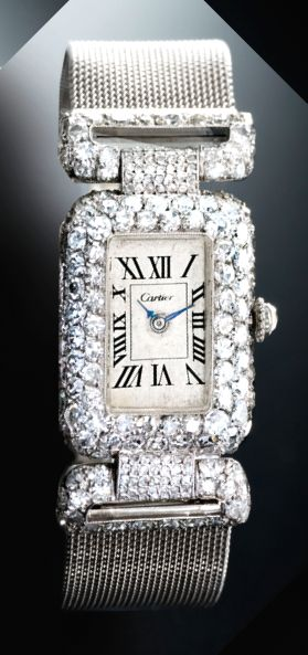 CARTIER/EUROPEAN WATCH & CLOCK CO., INC. A FINE AND RARE LADY'S PLATINUM AND DIAMOND-SET RECTANGULAR BRACELET WATCH WITH ARTICULATED LUGS CIRCA 1925 • oval manual-winding movement • silvered dial, Roman numerals, blued steel hands • rectangular case, platinum and pavé diamond-set bezel with rounded edges, diamond-set crown, case back secured by four screws, articulated modified t-bar lugs • dial signed Cartier, movement and inside of case signed European Watch & Clock Co.