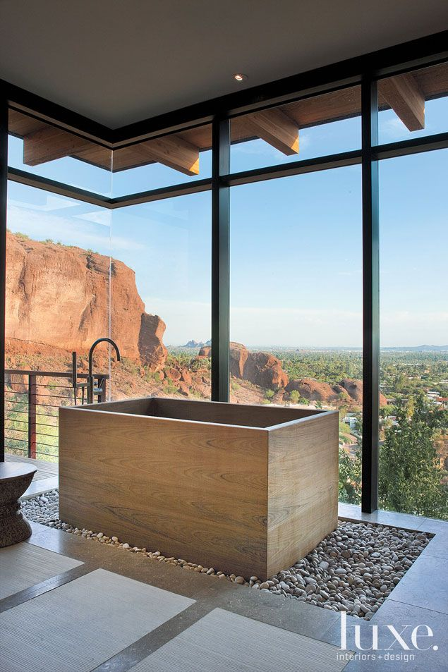 A custom Japanese soaking tub is wrapped in teak and enjoys commanding views of Camelback Mountain. The loose pebble floor allows water splashed out of the tub to drain easily.