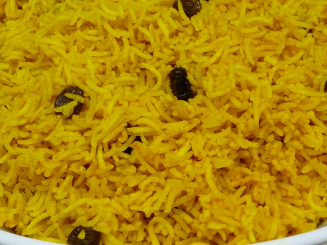 """Yellow rice is made by adding boiling water, turmeric, butter, salt, sugar, a piece of cinnamon stick, and raisins to regular white rice and simmering until all the liquid has been absorbed. It is traditionally served with Bobotie. Recipe in """"South African Cooking in the USA"""", page 105."""