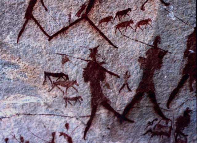 San Bushman in back, in front clothed people with sticks / assegai and herds? Hunters - note hunted hanging from stick