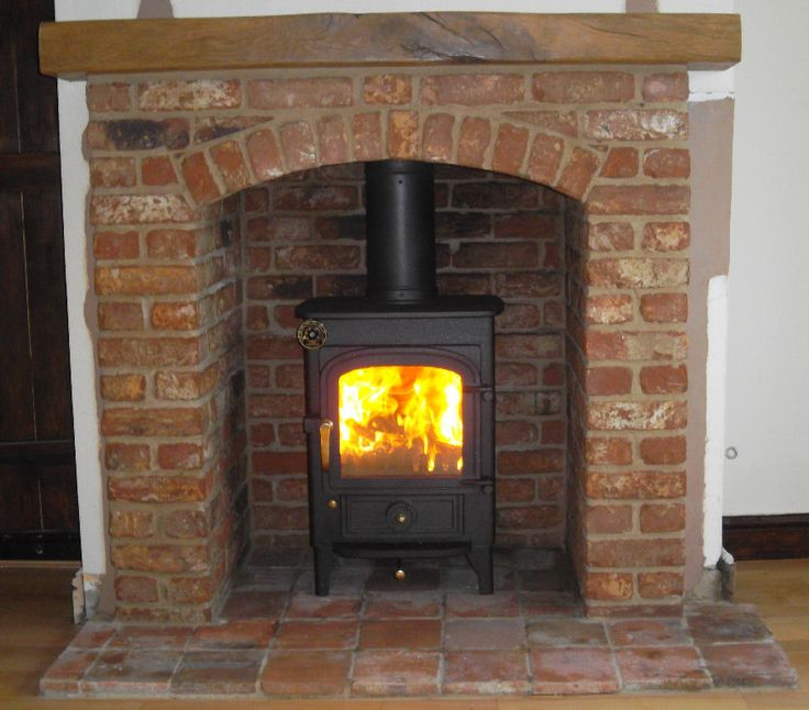 Clearview Pioneer wood burning stove with brick arch and beam. Nice stove - great surround!