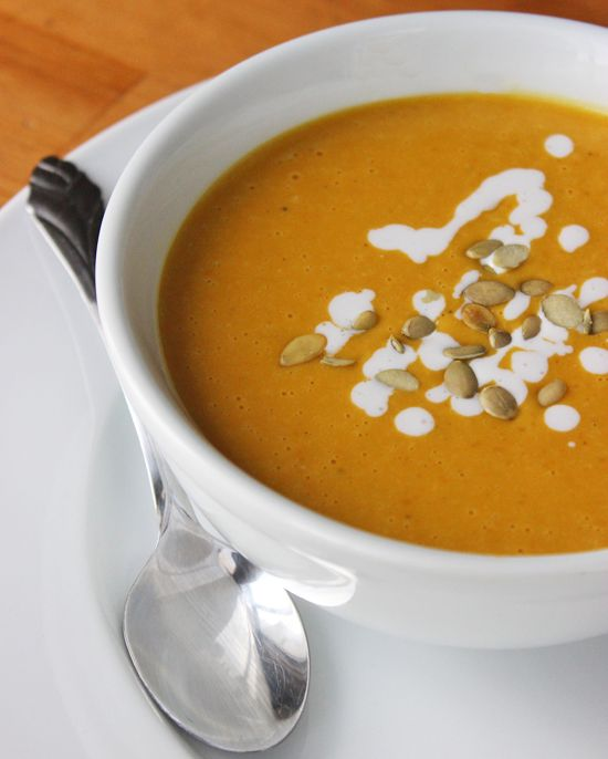 Healthy Pumpkin Soup Recipe | 1 1/2 tablespoons extra-virgin olive oil 1 cup chopped onion 3 garlic cloves, minced 3 cups solid-pack pumpkin, canned 2 cups low-salt vegetable broth 2 teaspoons sugar 1/2 teaspoon ground allspice 1/2 teaspoon dried crushed red pepper 1 1/2 cups unsweetened coconut milk, divided Salt and pepper Pepitas, for garnish