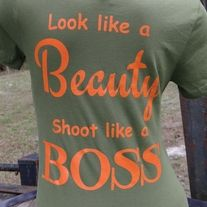 Olive t-shirt with orange print.  4.2 oz 100% combed and ring-spun cotton, slightly longer body length, fitted silhouette.  Extremely soft and lightweight.  Shoot, shooter, guns, girls with guns, hunter, huntress, firearm, nra, weapon, glock, smith and Wesson, 9mm, caliber, billiards, pool, cue stick