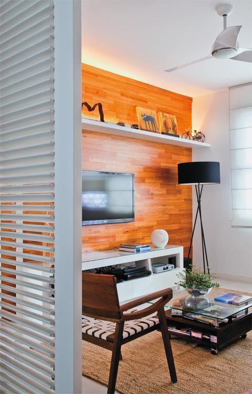 Entre o hall de entrada, a sala de estar e a cozinha, as arquitetas projetaram uma divisória de madeira (com 1,07 x 2,37 m e aletas articuladas de 6 x 1,8 cm). A peça separa os ambientes, mas deixa passar a luminosidade. Isso permitiu abrir mão do branco total numa das paredes da sala, cuja superfície de 4,47 x 2,87 m exibe acabamento de lâminas de peroba-do-campo. Toda a marcenaria é da Modelar Móveis.