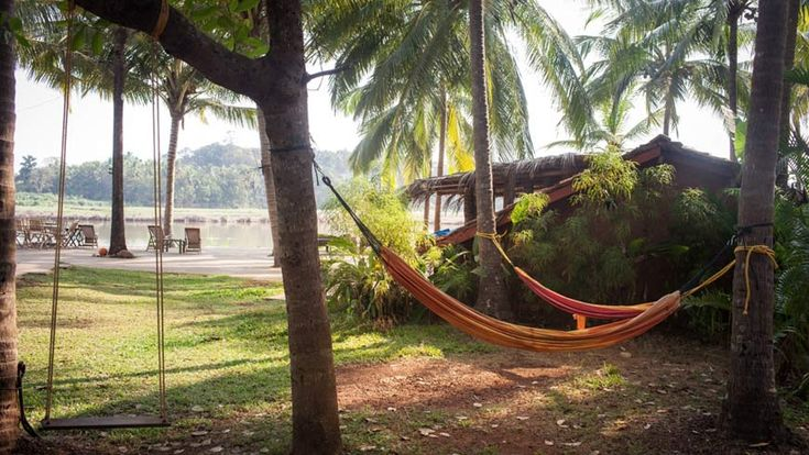 Hammocks looking out to the river that flows down to the sea from here in Olaulim, north Goa. More info: https://www.tripzuki.com/hotels/olaulim-backyards-goa/