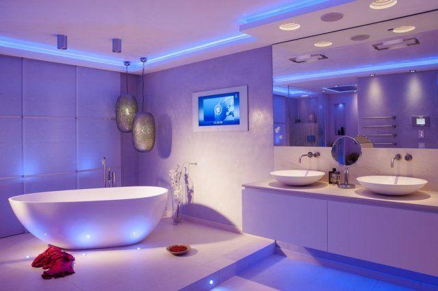 un éclairage LED et une baignoire îlot blanche dans la salle de bains