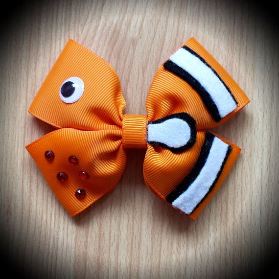 Finding Nemo Disney Character Inspired Hair Bow.  Orange Grosgrain Ribbon Decorated with Black and White Felt Fish Accents, Eye feature and rhinestones.  Mounted on an alligator clip.  I can do custom bows, just let me know if youd like something specific.  Price is for single bow.