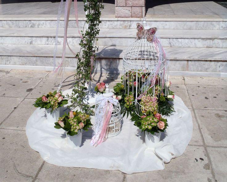 Μια ρομαντική σύνθεση με πράσινες και ροζ αποχρώσεις με vintage χαρακτήρα και πρωταγωνιστές ένα αναπαλαιωμένο κλουβί και μια πεταλούδα. Η σύνθεση διακοσμείται υπέροχα από φρέσκα λουλούδια, όπως τριαντάφυλλα και πρασινάδες και δαντελένιες κορδέλες.