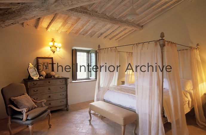 A large four poster bed with floating curtains in a rustic for Rustic elegant bedroom