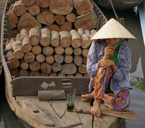 Woman on boat with wood and tea; Rach Gia, Mekong River Delta, Vietnam