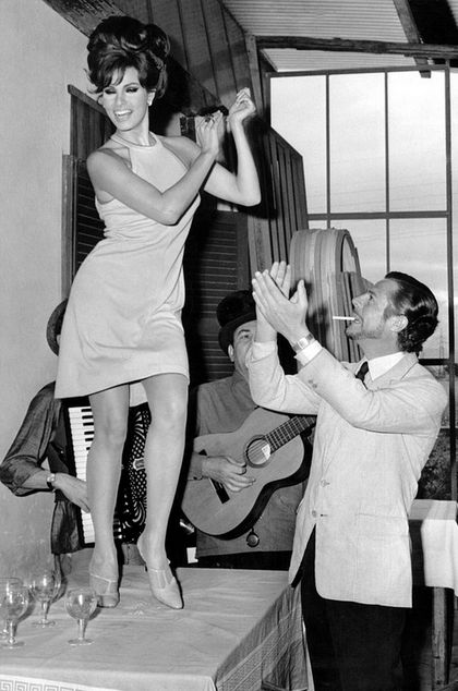 Raquel Welch dancing on a table while Marcello Mastroianni claps, 1966