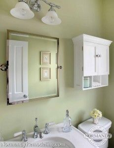 Storage ideas for a small powder room:  white cabinet over the toilet and medicine cabinet as well.  Created by Normandy Designer Vince Weber.