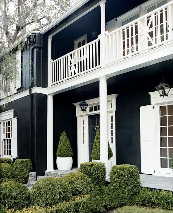black painted house with white windows and balustrade