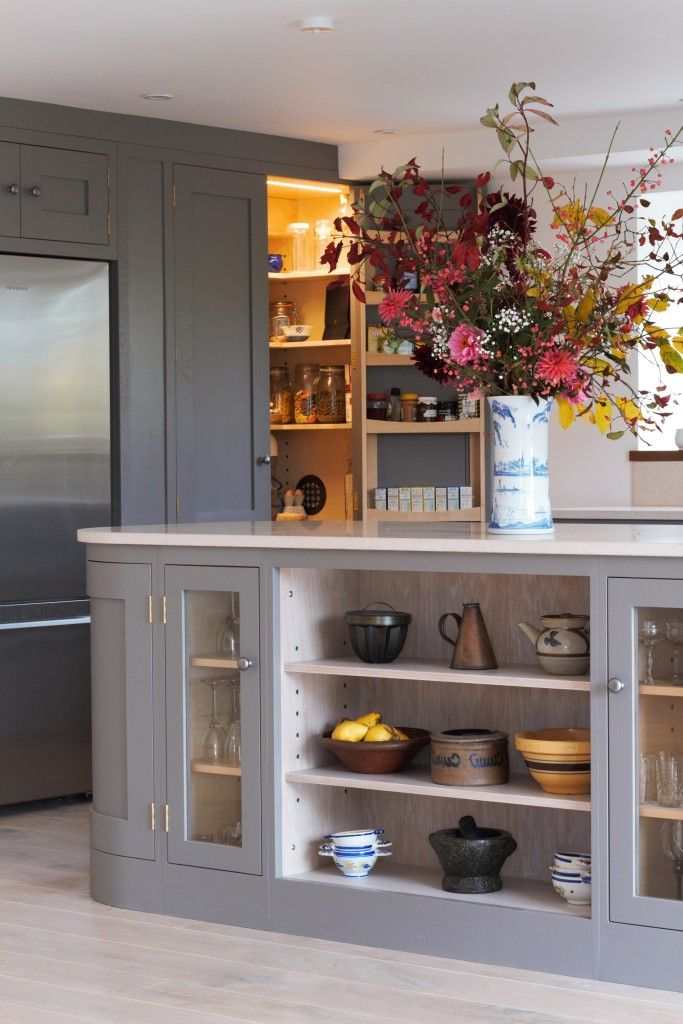 A beautiful open plan barn conversion. A shaker style kitchen painted in Farrow & Ball moles breath with a curved centre island with marble and oak worktops. The open larder cupboard with internal lighting is visible.
