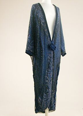 Midnight Blue Opera Coat   1920s   Of fine black net over blue silk, cobweb embroidered with small jet, blue and clear glass beads, in swirling pattern along cuffs of loose dolman sleeves and along all edges, trimmed in blue velvet and fastened at low front with velvet flower, size 8